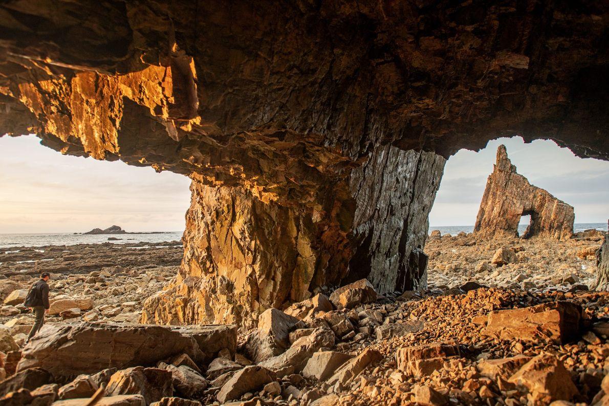 Na Playa de Campiechos, o sol poente e a maré baixa revelam a entrada de uma ...