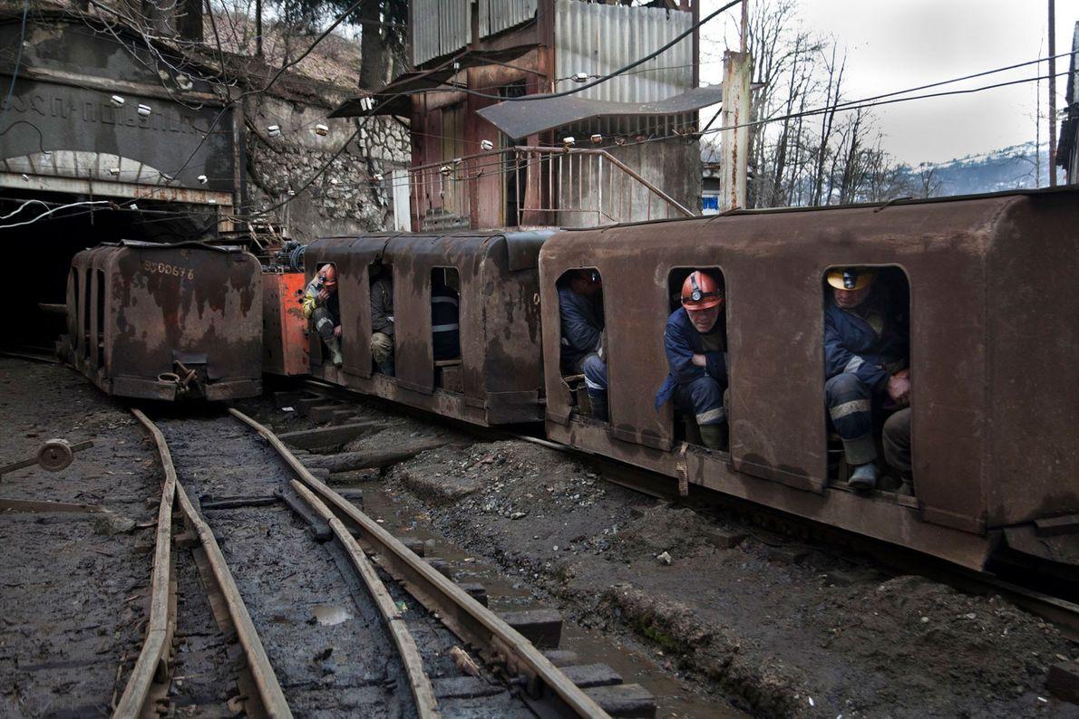 Mineiros instalados num vagão a caminho do túnel da mina