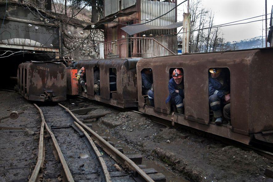 Mineiros instalados num vagão a caminho do túnel da mina.