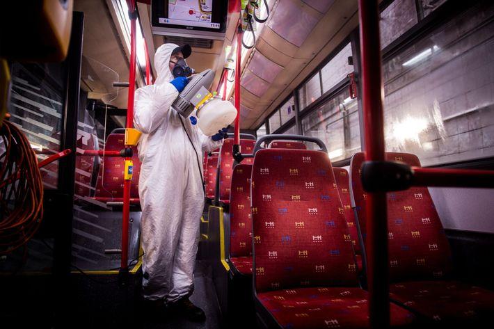 Um trabalhador com um fato protetor desinfeta o interior de um autocarro, numa estação de lavagem ...