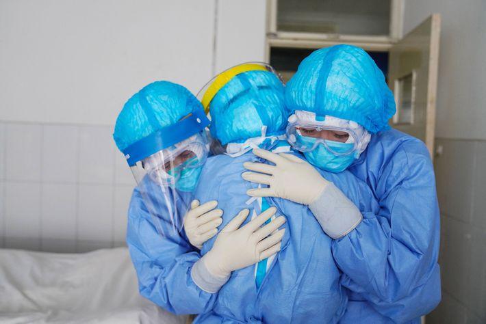 Membros da equipa médica abraçados numa ala de isolamento de um hospital em Zouping, na província ...
