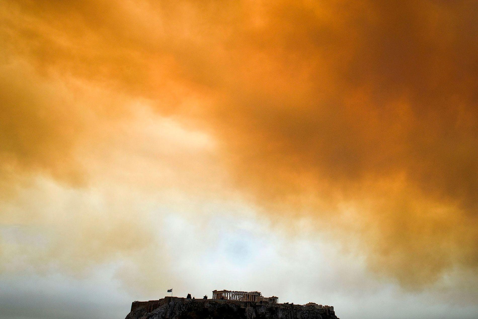 O Parthenon, o antigo templo da Acrópole em Atenas, na Grécia, eleva-se no horizonte, sobre um cenário de fumo proveniente de um incêndio em Kineta, perto de Atenas.