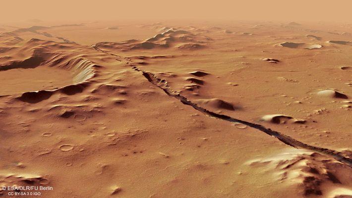 Esta fratura de Cerberus Fossae estende-se ao longo de colinas e crateras já preexistentes, sugerindo que ...