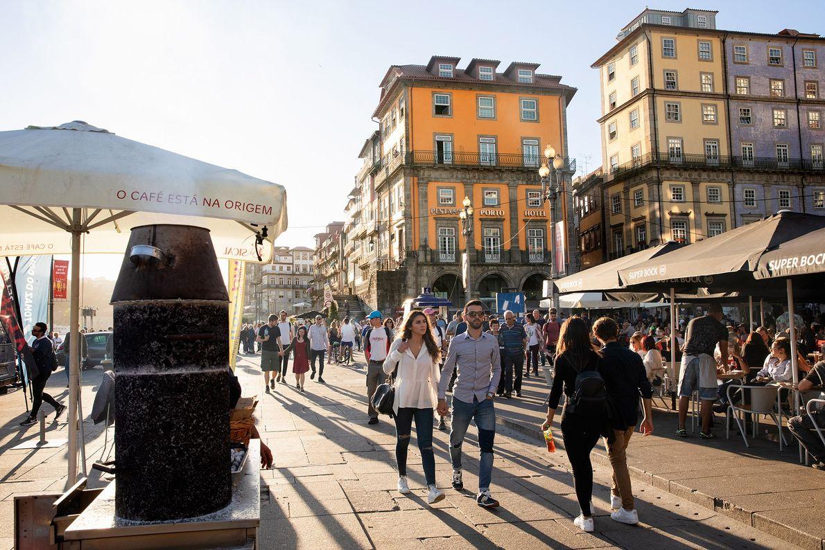 Vendedores de castanhas e esplanadas de cafés, com pessoas a passear, na marginal do Porto, numa ...