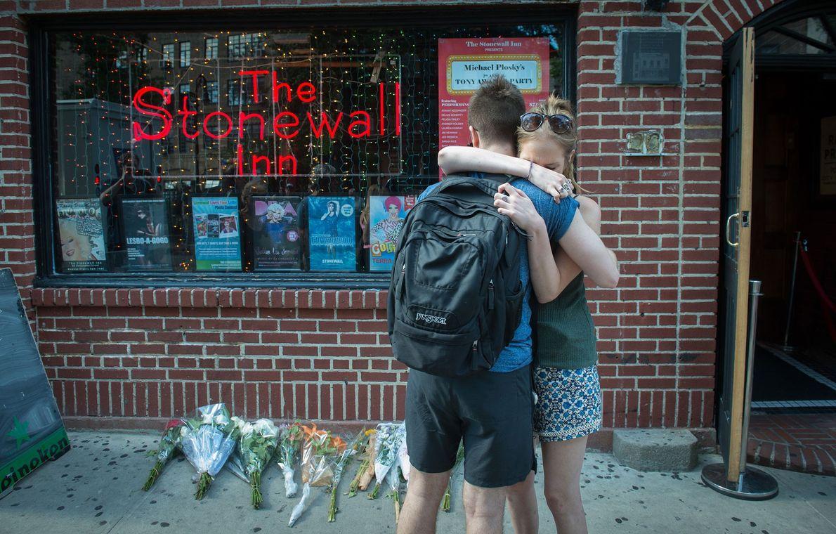 Dois jovens abraçam-se no exterior do bar The Stonewall Inn