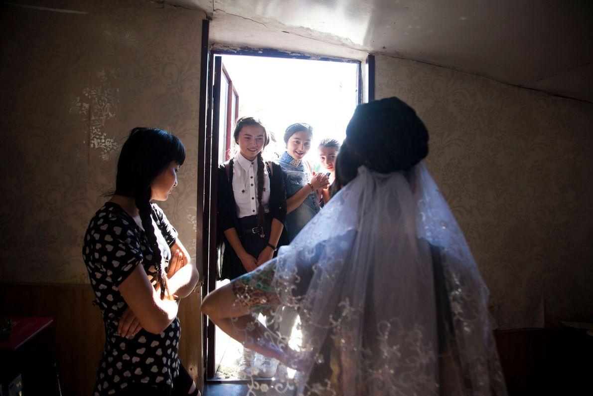 Fotografia de jovens raparigas a admirarem o vestido de noiva da amiga.
