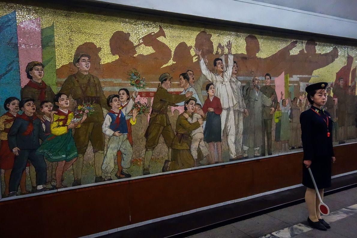 Uma pessoa que espera o comboio fica em frente a um mural comemorativo da independência da ...