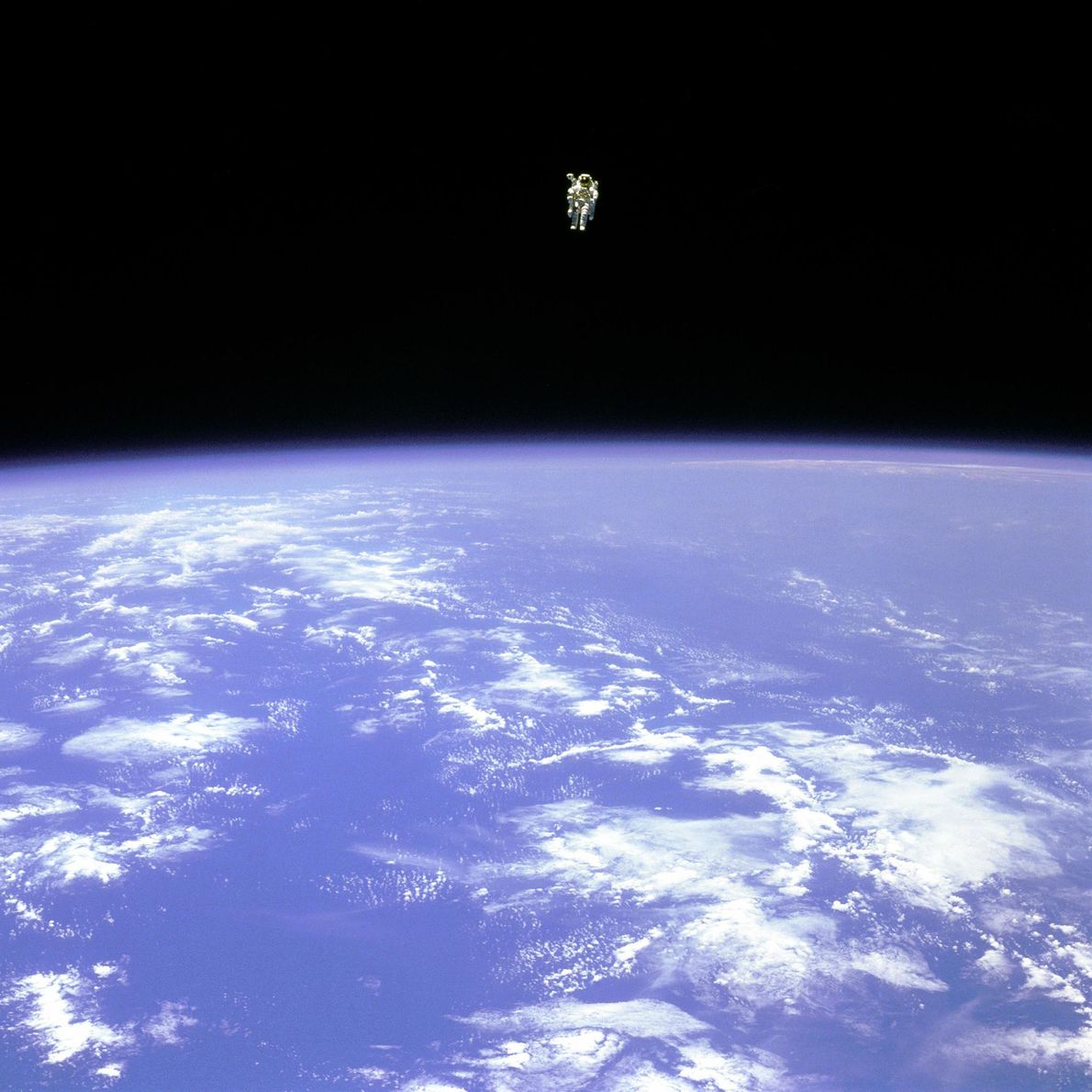 O astronauta Bruce McCandless paira sobre o planeta Terra