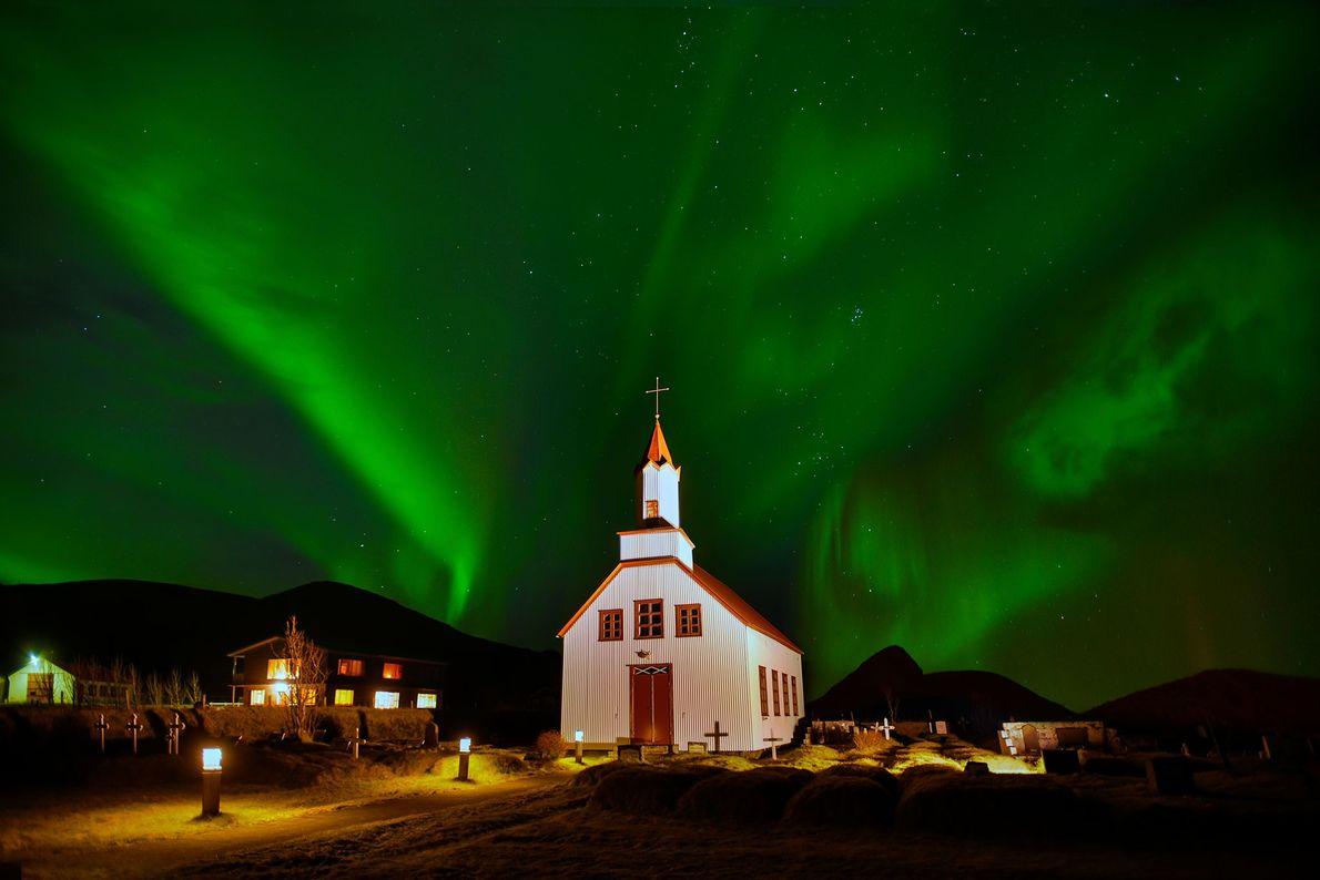 A aurora boreal faz com que o céu fique verde por trás de uma igreja na …