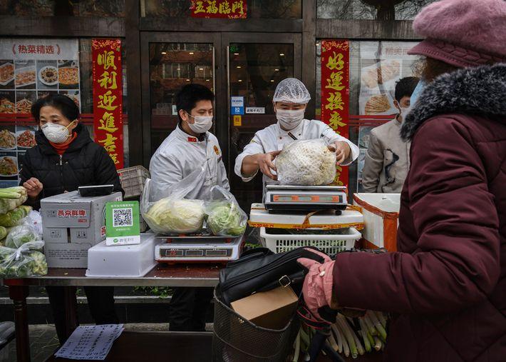 Em Pequim, os comerciantes usam máscaras faciais enquanto vendem vegetais. Um estudo de 2014 constatou que ...