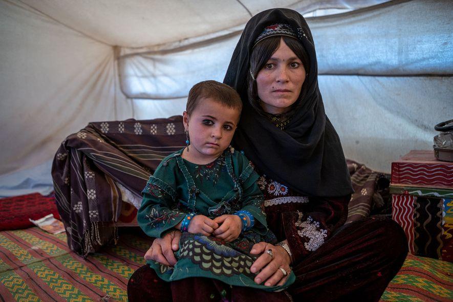 Fariba, de 5 anos, sentada ao colo da mãe, Fatemeh, na tenda improvisada da sua família, ...