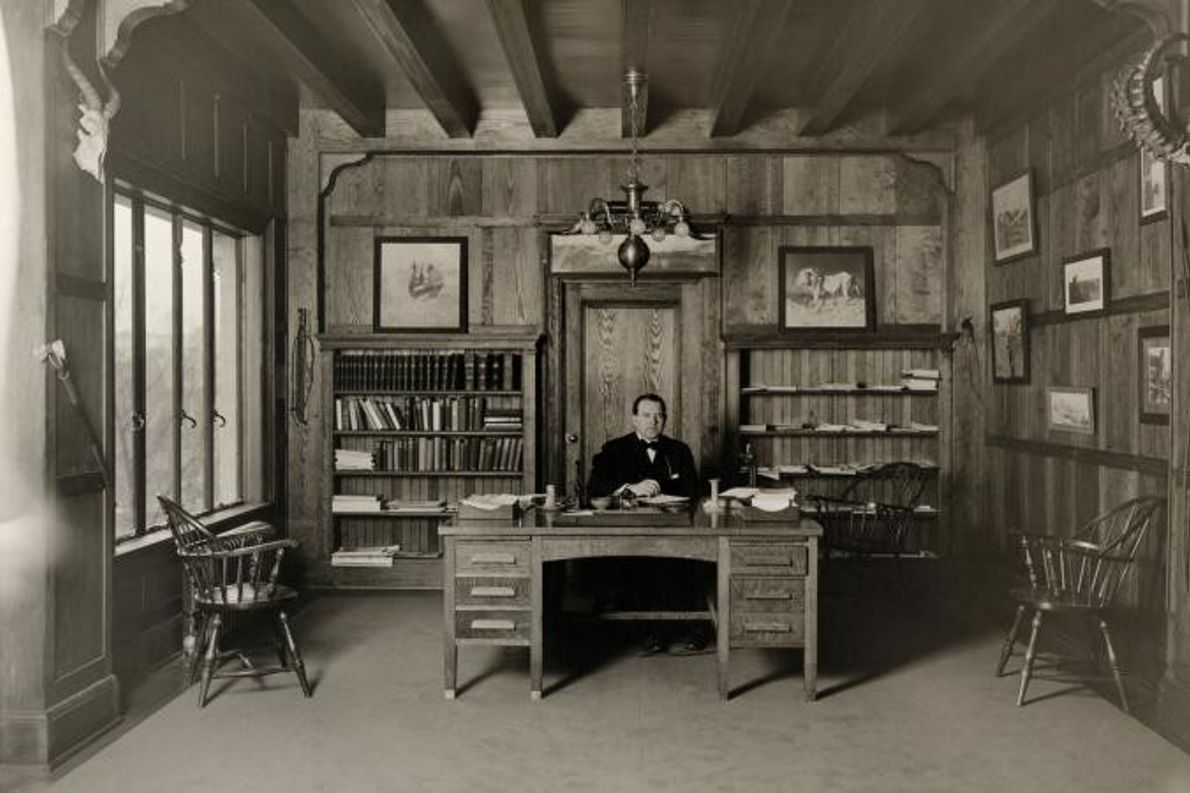 John Oliver LaGorce, editor associado da revista da National Geographic, é fotografado sentado à secretária.