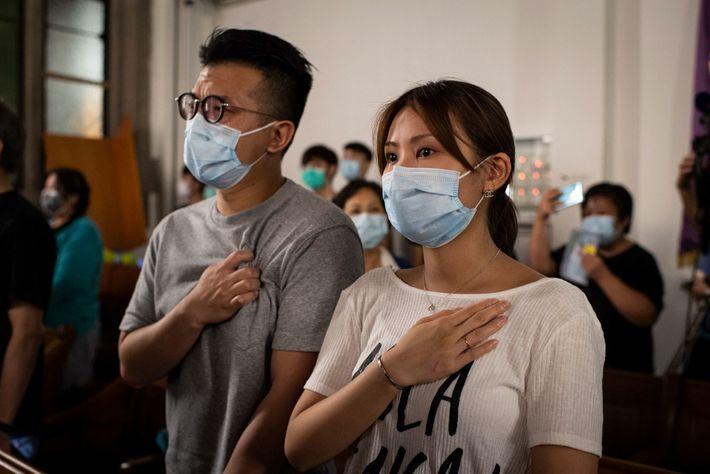 """Na Igreja da União de Kowloon, um homem e uma mulher comovem-se enquanto cantam """"Glória a ..."""