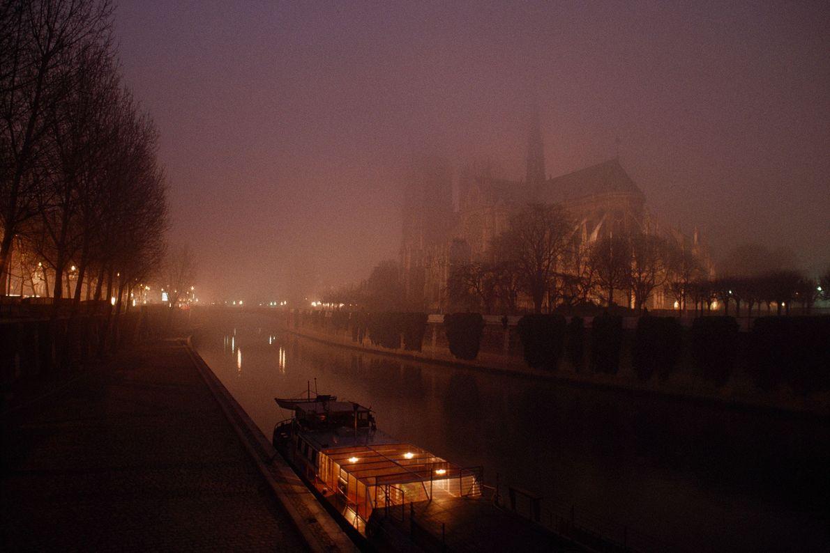 Uma vista noturna, da década de 1980, mostra a catedral vista do Sena.