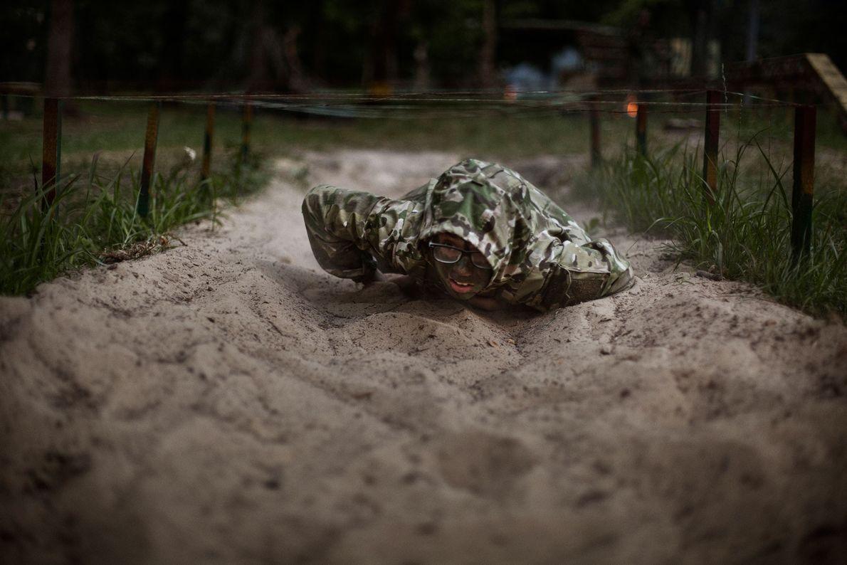 Mathew, 11 anos, rasteja sob arame farpado durante os exercícios militares no acampamento LIDER.