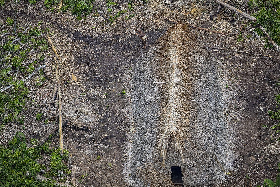 Imagem de uma cabana comprida e com telhado de palha, na selva amazónia, vista de cima
