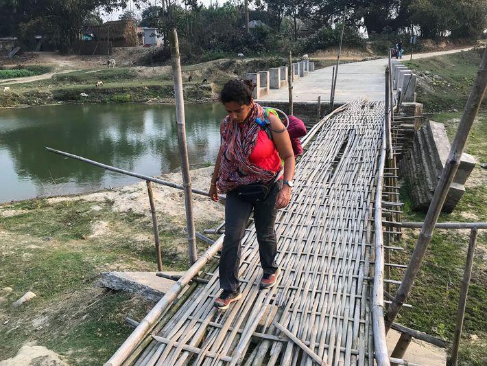 Priyanka Borpujari atravessa uma ponte de bambu, no estado indiano de Bengala Ocidental.