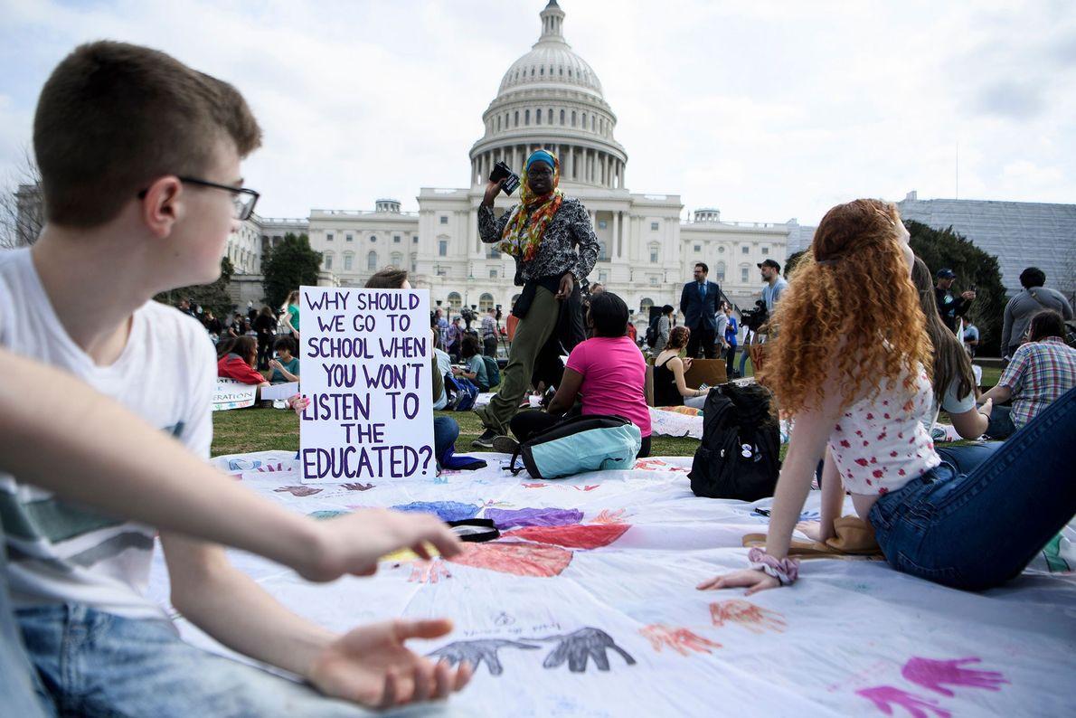 Os jovens grevistas levaram cartazes e pintaram telas enormes de tecido, no relvado em frente ao ...