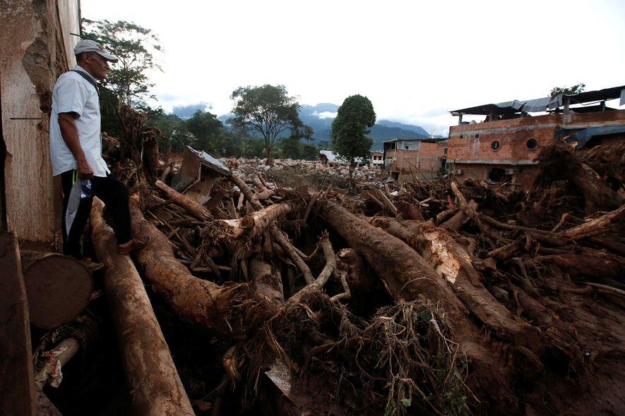 Um homem olha para uma área destruída depois das chuvas intensas que causaram o transbordo de ...