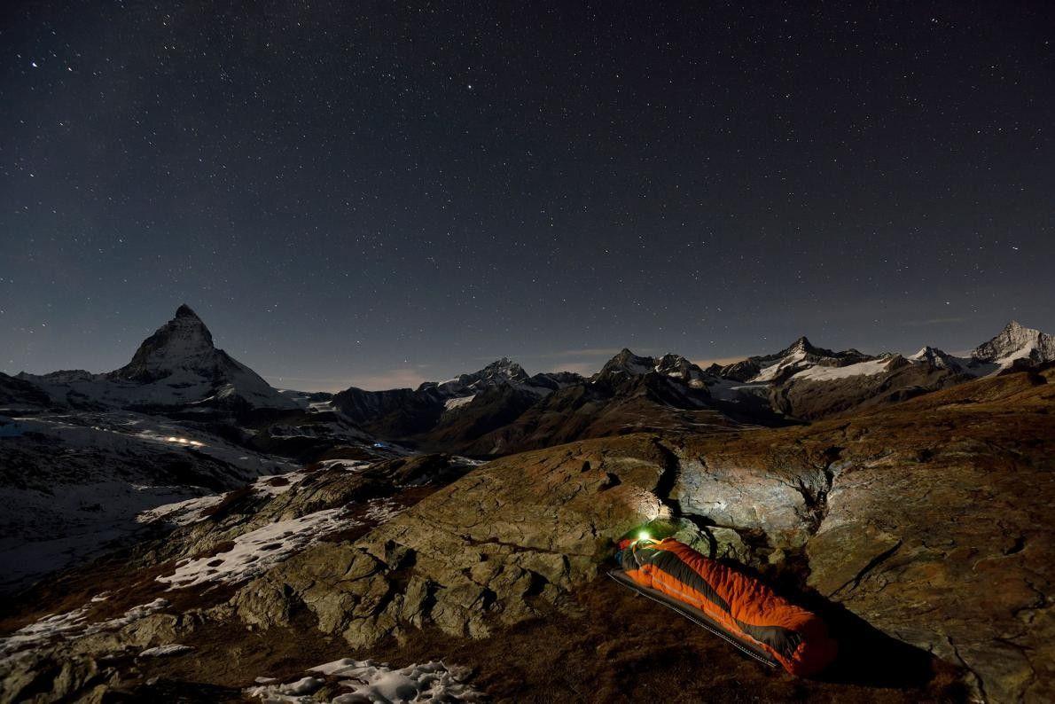 Um explorador italiano aconchega-se no saco-cama, com o majestoso Matterhorn como cenário de fundo.