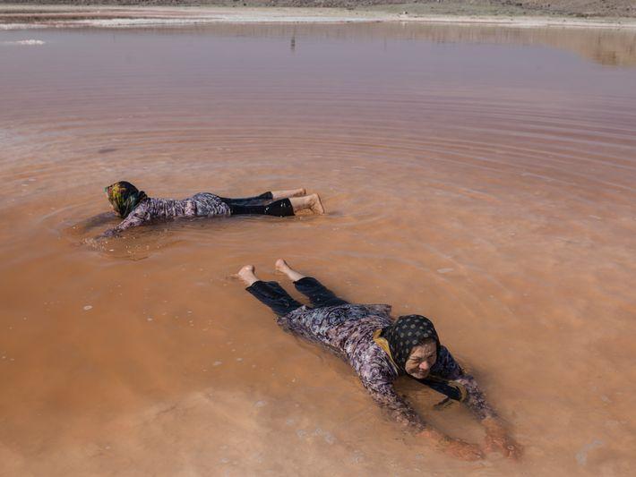 Duas mulheres banham-se nas águas vermelhas do que resta do Lago Urmia