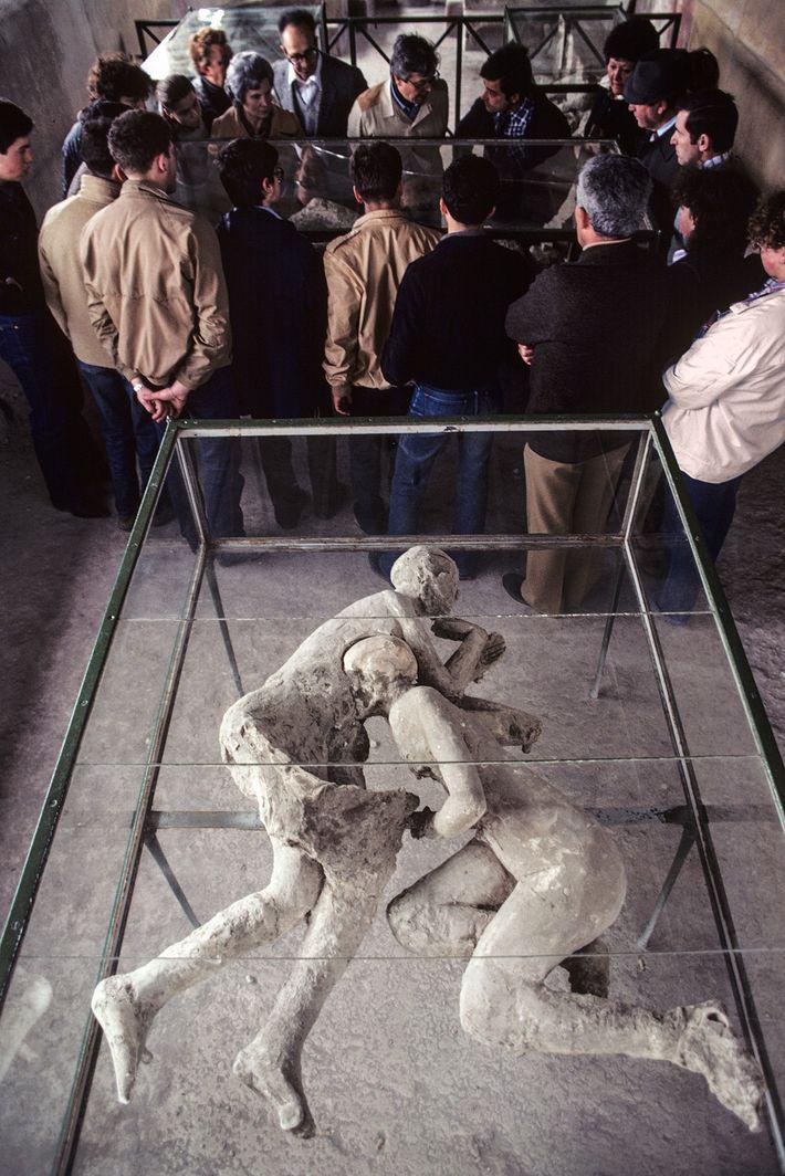 Um grupo de pessoas estuda os corpos na Casa de Cryptoporticus enquanto percorre as ruínas de ...