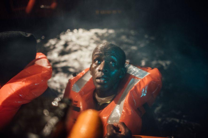Os evacuados são transferidos de um bote semi-rígido insuflável para o MS Aquarius, que pode transportar ...