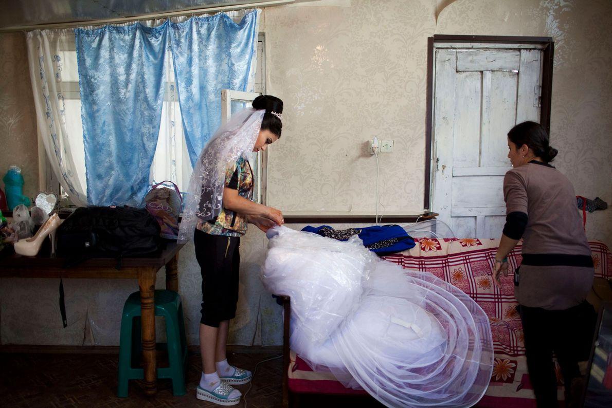 Imagem de uma noiva adolescente a arranjar o vestido que vai usar no seu casamento
