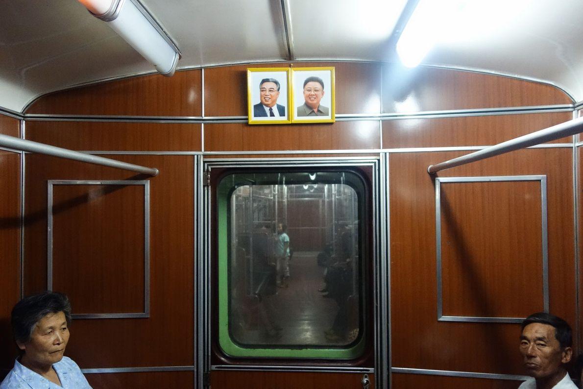 Retratos dos líderes supremos, pai e filho, Kim Il Sung e Kim Jong Il estão pendurados ...