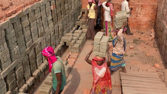 Workers at the ABC brickyard in the northeastern state of Assam fill pit furnaces with unfired ...