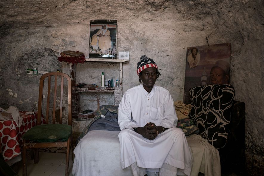 Mbacke deixa-se fotografar sentado sobre a sua cama no interior de uma gruta em Sacromonte, onde ...