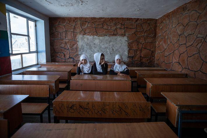 Raparigas afegãs à espera que a aula comece, numa escola secundária para raparigas, na província de ...