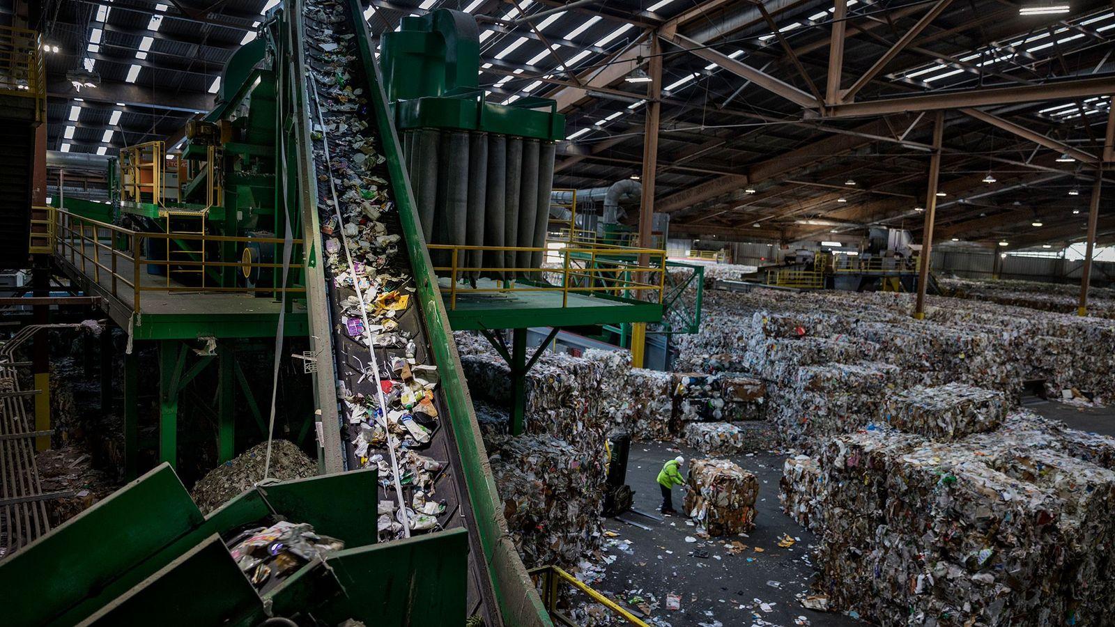 Um tapete rolante a levar plástico para a triagem numa instalação de reciclagem em São Francisco, ...