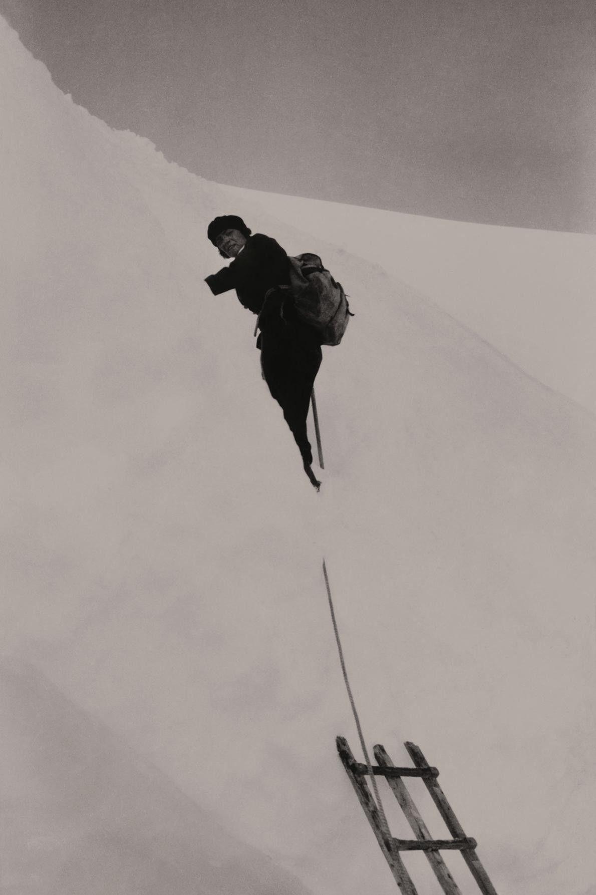 Uma alpinista usa uma escada para atravessar uma fenda em Jungfrau, nos Alpes berneses.