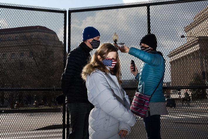 Uma família com máscaras com a bandeira dos EUA espreita através da vedação de segurança para ...