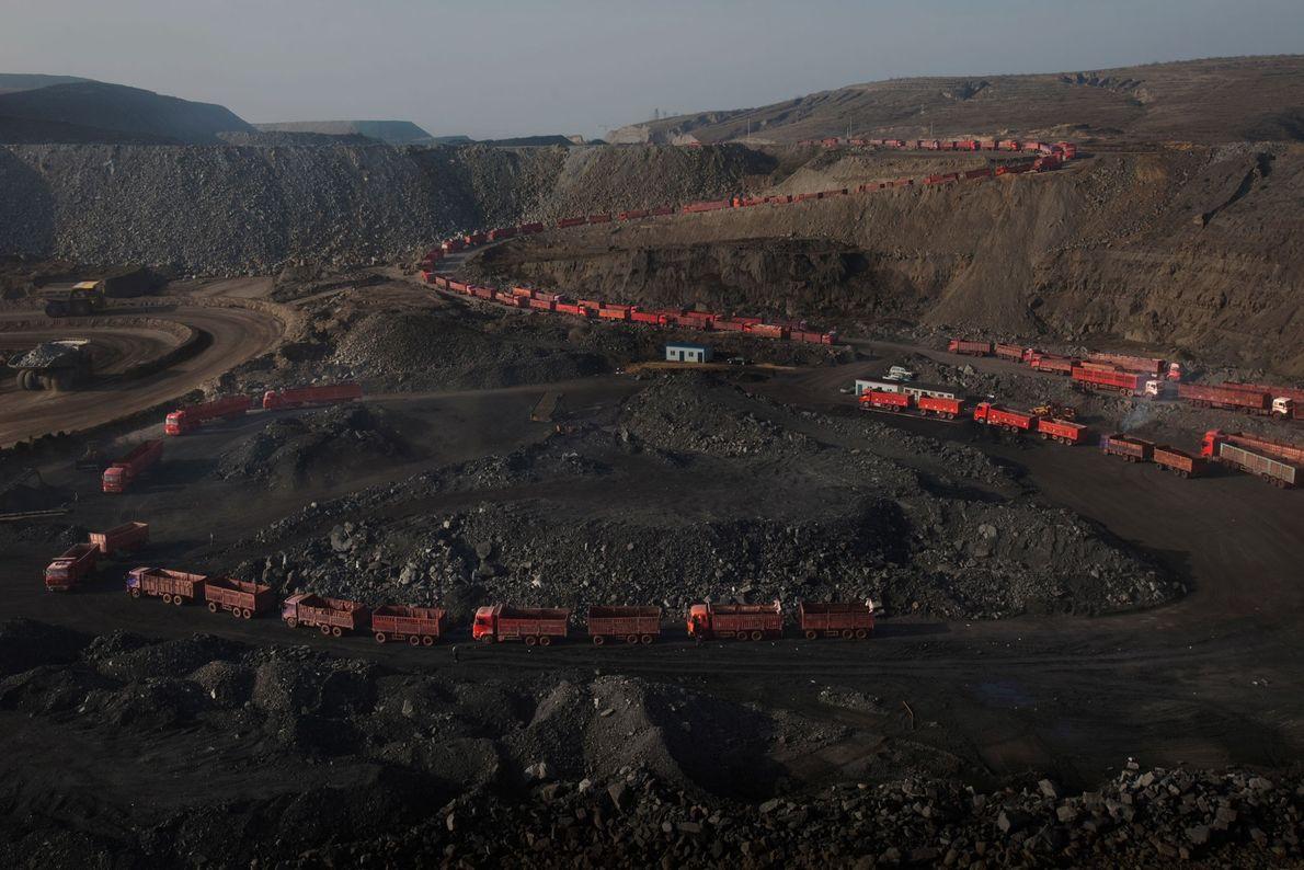 Camiões aguardando numa longa fila de espera para serem carregados com carvão.