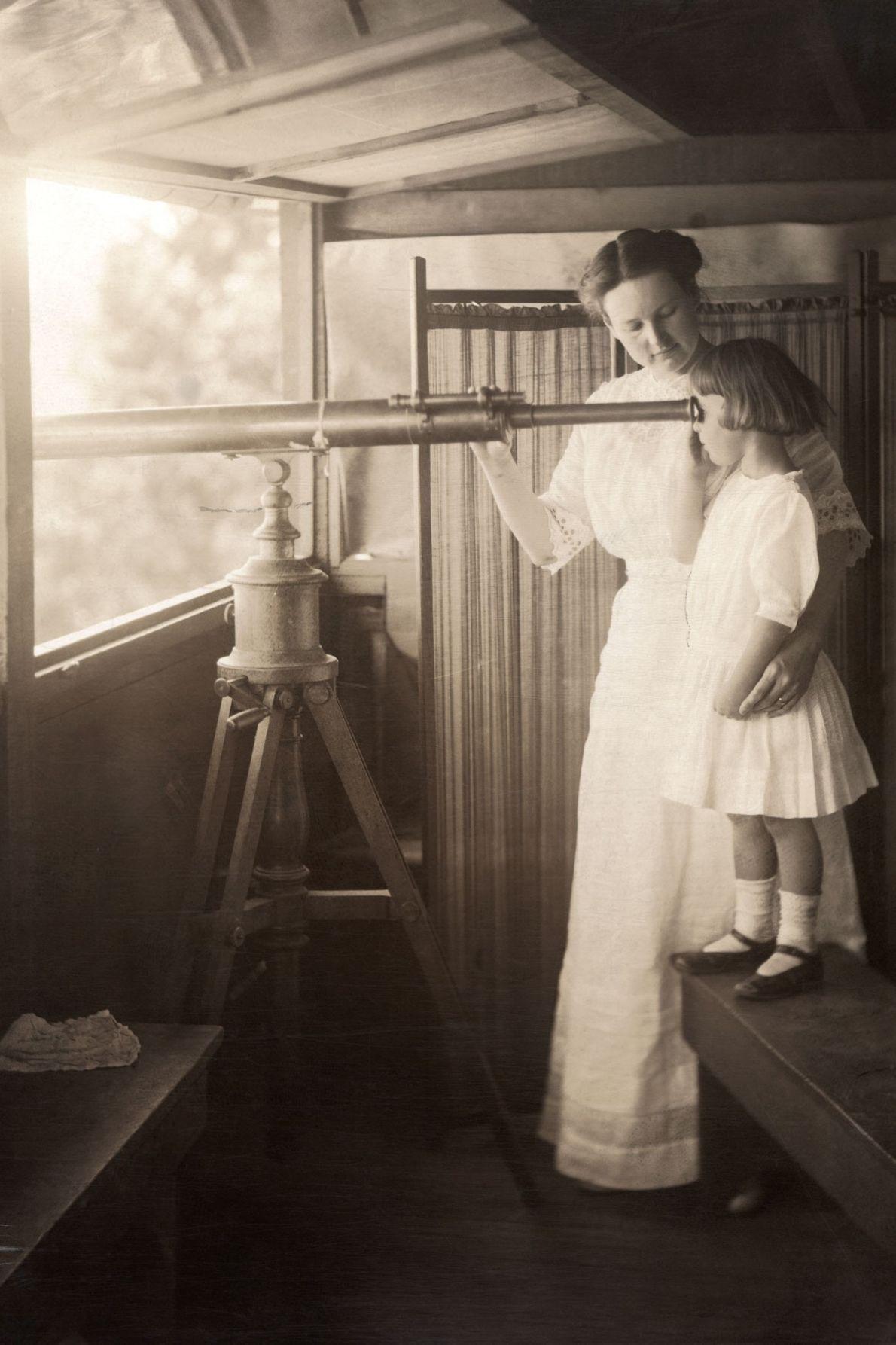 Uma mãe e a filha observam um sinal de incêndio.