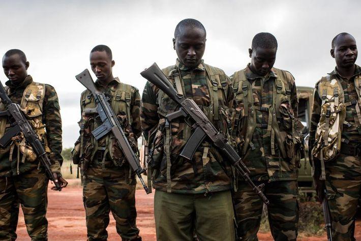 Guardas dos Serviços de Vida Selvagem do Quénia rezam antes de uma operação de colocação de ...
