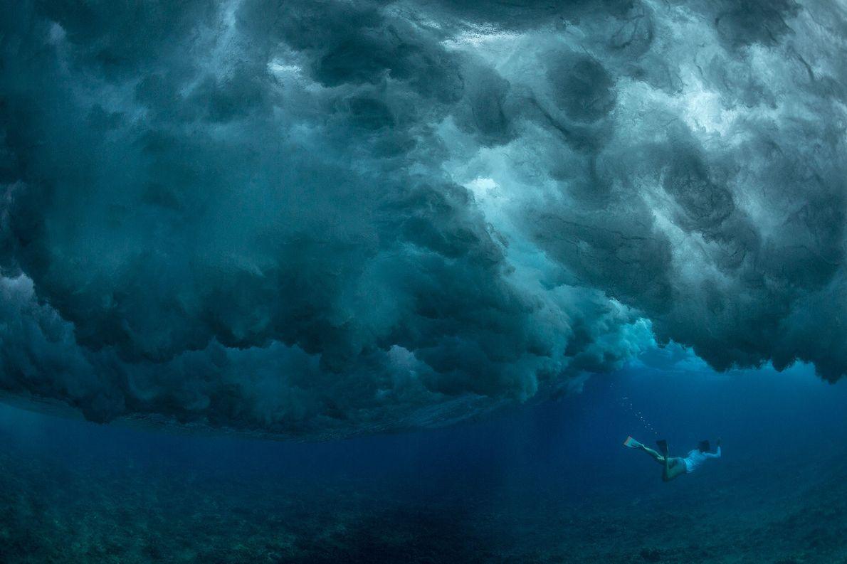 Um mergulhador aguarda nas águas estáticas, sob o rebentamento das ondas na Ilha Oahu, no Havai.