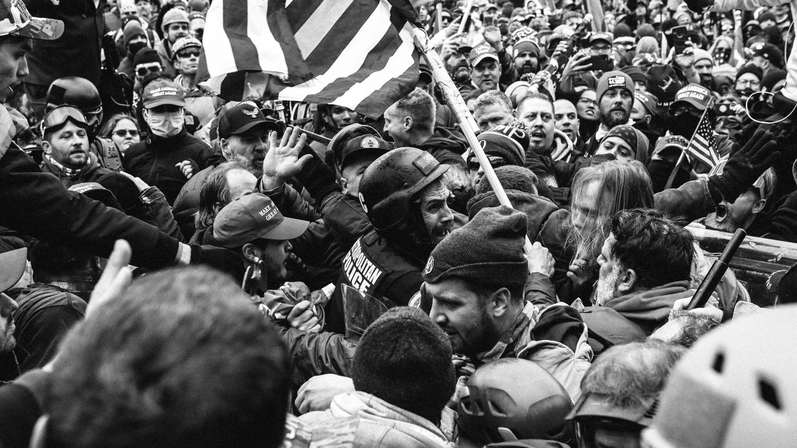 Um polícia de Washington D.C. (de capacete) foi violentamente empurrado dos degraus do Capitólio dos EUA ...