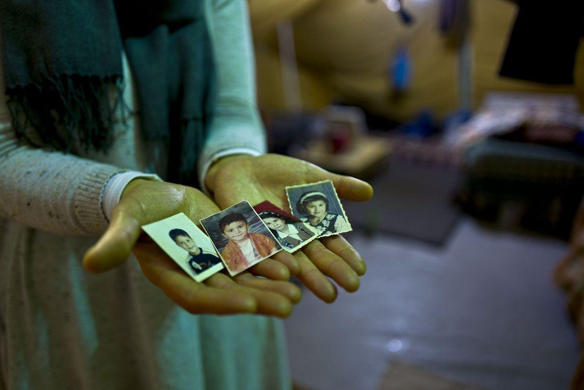 Mulher com as fotografias dos quatro filhos.