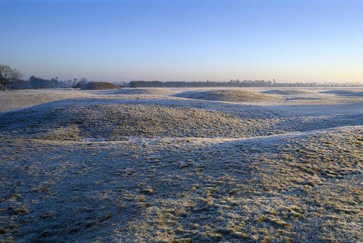 Uma vista dos montes funerários de Sutton Hoo cobertos de geada ao amanhecer. Parte dos túmulos ...