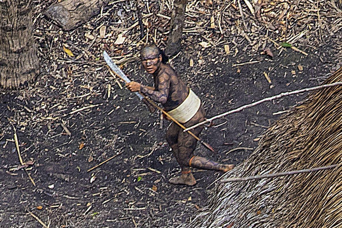 Imagem de um indígena com corpo pintado a transportar um machete