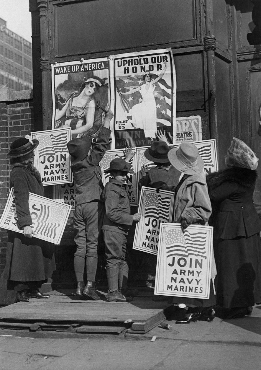 Mulheres e crianças penduram cartazes a pedir aos americanos para se alistarem no exército.