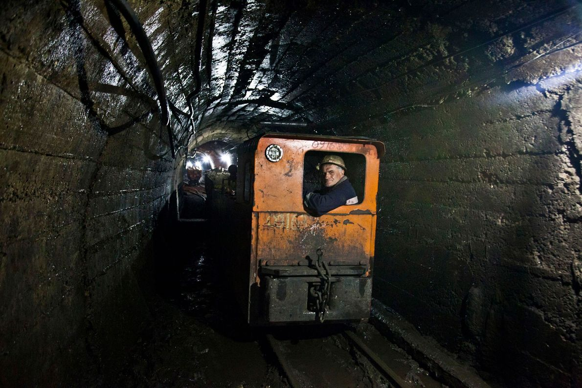 Mineiro senta-se num vagão a caminho do túnel
