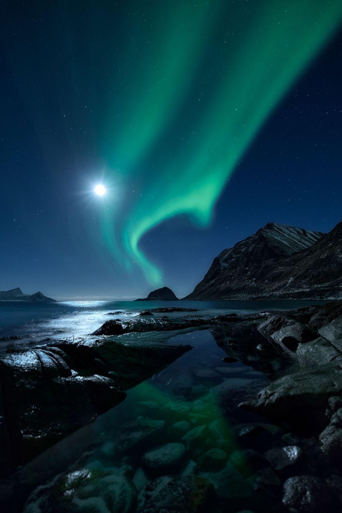 A lutar para não ser ofuscada por uma superlua brilhante, a aurora boreal brilha sobre um ...