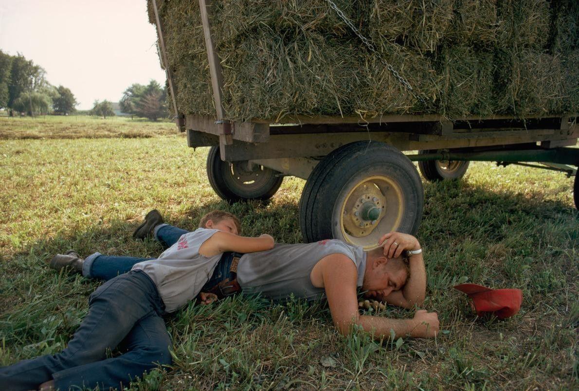 Dois agricultores descansam perto de um atrelado.