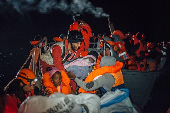Um voluntário nas operações de salvamento entrega um bebé à mãe.