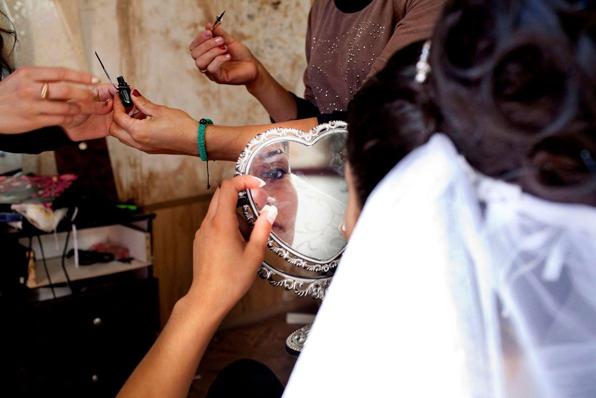 Imagem de uma noiva adolescente a maquilhar-se no dia do seu casamento