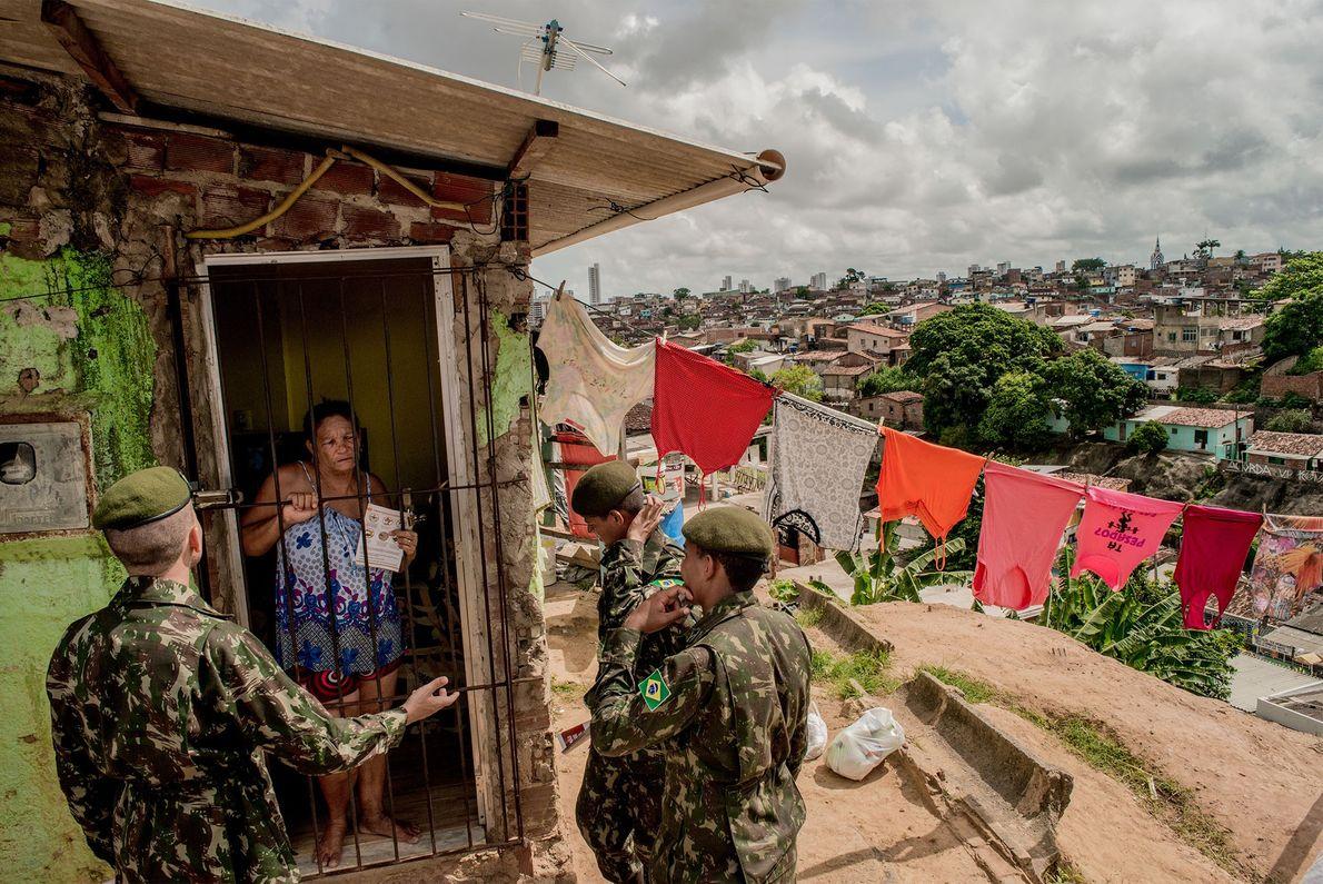 Soldados a explicar a uma mulher no bairro Alto José Bonifácio, no Recife, como evitar a ...